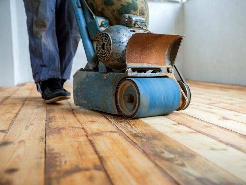 Een parketvloer wordt bij renovatie intensief geschuurd.